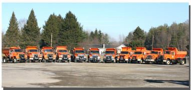 Dumptrucks lined up together in a parking lot